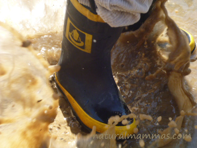 mud boots splashing in puddles playing in nature