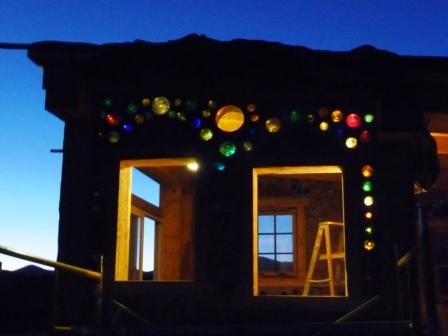 cordwood house at night with recycled glass windows shining
